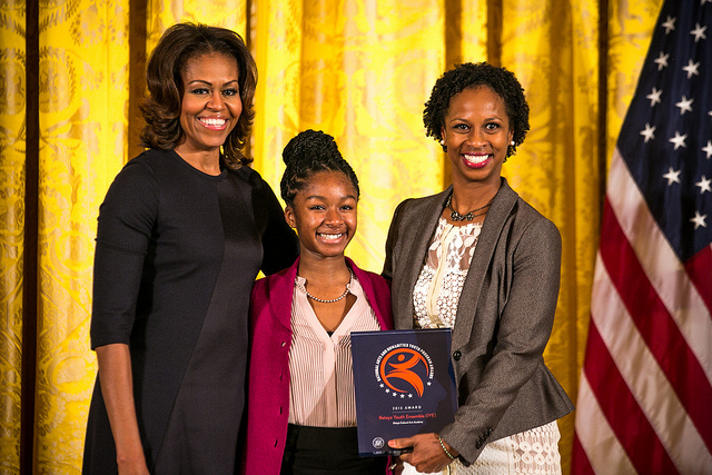 Ifetayo Youth Ensemble representatives Isoke Senghor (center) and Kwayera Archer-Cunningham (right) accept the 2013 National Arts and Humanities Youth Program Award from First Lady Michelle Obama. Photo credit: Ralph Alswang.