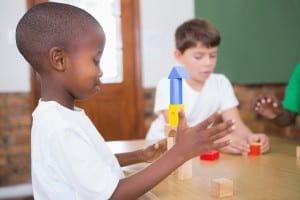 Cute pupils playing with building blocks