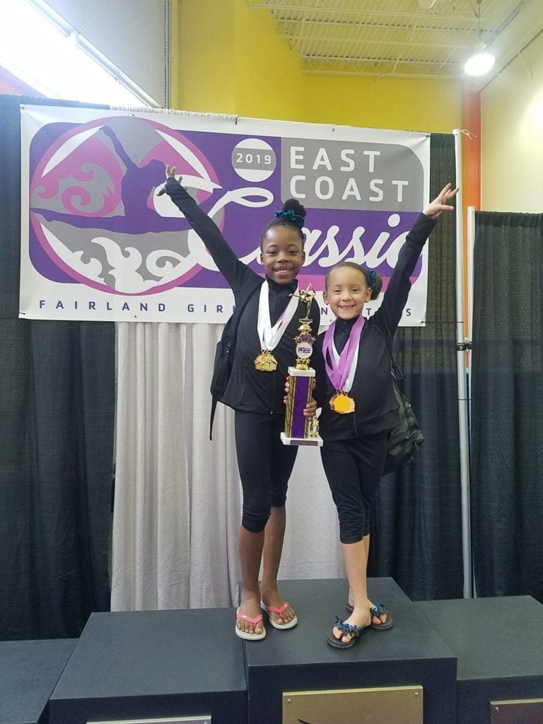 Brielle shares the spotlight with her friend and teamate after their gymnastics meet.